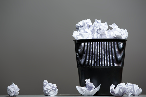 Recycle bin filled with crumpled papers. Gray background,